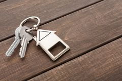 Wiązka klucze z domem kształtował keychain na brown drewnie Zdjęcia Royalty Free