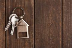 Wiązka klucze z domem kształtował keychain na brown drewnie Obrazy Stock