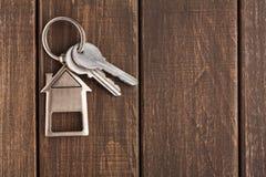 Wiązka klucze z domem kształtował keychain na brown drewnie Zdjęcie Royalty Free
