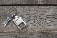 Wiązka klucze z domem kształtował keychain na nieociosanym drewnie Zdjęcie Stock