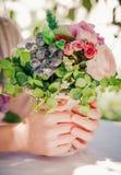 Wiązka lekka lato miękka część kwitnie z zielonymi liśćmi w kobiet rękach Natury pogodny tło Selekcyjna ostrość Obrazy Royalty Free