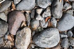 Wiązka otoczaków kamienie na ziemi z liśćmi pośrodku Odgórny widok Zdjęcie Royalty Free
