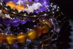 Wiązka semiprecious gemstone bransoletki na czarnym tle - kornalina, ametyst, kwarc zdjęcia royalty free