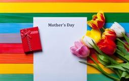 Wiązka tulipany, prezent i prześcieradło papierowy lying on the beach na stole, Obrazy Royalty Free