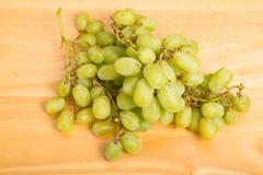 Wiązka Zieleni Beznasienni winogrona na drewno stole Obrazy Stock