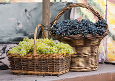 Wiązki biali i czarni winogrona w łozinowym koszu Obrazy Stock