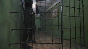 Więźniarski strażnik w taktycznym mundurze otwiera bramy, 4k zbiory