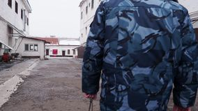 Więźniarskiego oficera odprowadzenie w inter jardzie w rosyjskiej penitencjarnej koloni, więzienie z kluczami przy zimą zdjęcie wideo