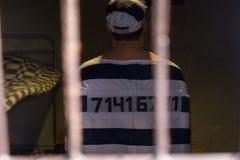 Więzień jest ubranym więzienie mundur z szył jego numerową pozycję Fotografia Royalty Free