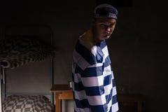 Więzień patrzejący z powrotem z gniewnym spojrzeniem w małym ciemnym więzieniu Zdjęcie Stock