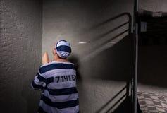 Więzień siedzi w kącie i ono modli się w małym więzieniu Zdjęcia Stock