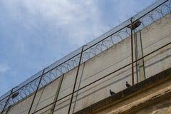 Więzienie ściana przeciw niebieskiemu niebu z chmurami fotografia stock