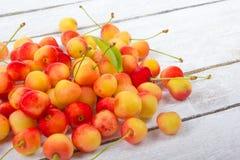 Wiśnia w pucharze Świeża żółta wiśnia Wiśnia na białym drewnianym tle Pojęcie zdrowa dieta jagody Obrazy Royalty Free