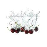 Wiśnie bryzgają na wodzie, odosobnionej na białym tle Obrazy Stock