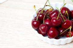 Wiśnie w biały pucharze tła jagod wiśnia dotyka utrzymania biały - zdrowy łasowania i jedzenia pojęcie fotografia stock