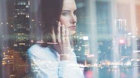 照片女商人佩带的白色衬衣,谈的智能手机 露天场所顶楼办公室 全景窗口,夜城市背景 Wi 免版税库存照片