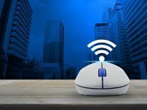 Technology and internet concept. Wi-fi button with wireless computer mouse on wooden table over modern office city tower, Technology and internet concept Stock Images