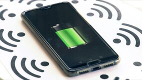 Wi-fi charging phone charger rotating with wireless symbols and battery icon background