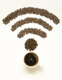 Wi-fi coffee. Creative concept photo of  a cup with coffee beans in the shape of wi-fi sign on white background Royalty Free Stock Image