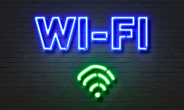 Wi-fi neon sign on brick wall background. Stock Image