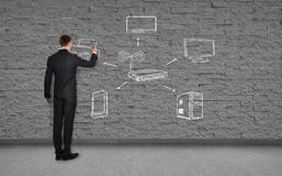 Wi-fi scheme. Businessman drawing wi-fi scheme  on brick wall Stock Photo