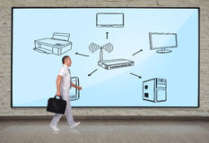 Wi-fi scheme. Businessmen walking at big plasma panel with wi-fi scheme royalty free stock image