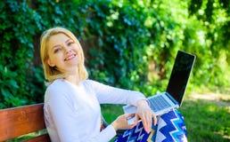 Wi fi sieci związku wolny dostęp Damy freelancer pracuje w parku Kobieta z laptopem pracuje plenerową, zieloną naturę, obraz royalty free