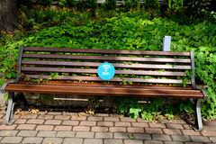 Wi-fi zone. Sing of a wi-fi zone in blue label on a bench in city park Royalty Free Stock Images