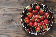 Wiśnia i truskawka w talerzu na drewnianym stole Fotografia Royalty Free