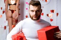 ?wi?tuje mi?o?ci niespodzianka, romantyczna Walentynka dnia prezent Prezent dla dziewczyny Atrakcyjny macho z prezentami świętuje obraz stock