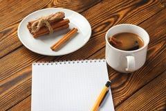 Wi?zka cynamon dzia? z arkan?, fili?anka kawy i notatnikiem dla pisa? na drewnianym tle w g?r?, obrazy stock