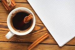 Wi?zka cynamon dzia? z arkan?, fili?anka kawy i notatnikiem dla pisa? na drewnianym tle w g?r?, fotografia royalty free