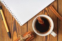 Wi?zka cynamon dzia? z arkan?, fili?anka kawy i notatnikiem dla pisa? na drewnianym tle w g?r?, obraz royalty free