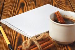 Wi?zka cynamon dzia? z arkan?, fili?anka kawy i notatnikiem dla pisa? na drewnianym tle w g?r?, zdjęcie royalty free