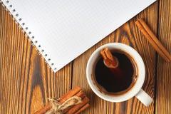 Wi?zka cynamon dzia? z arkan?, fili?anka kawy i notatnikiem dla pisa? na drewnianym tle w g?r?, obrazy royalty free