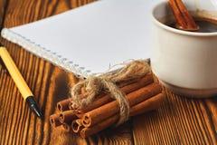 Wi?zka cynamon dzia? z arkan?, fili?anka kawy i notatnikiem dla pisa? na drewnianym tle w g?r?, zdjęcie stock