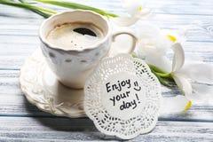 Wiadomość Cieszy się twój dzień z filiżanką coffe o i piękni kwiaty Fotografia Royalty Free