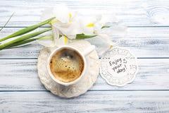 Wiadomość Cieszy się twój dzień z filiżanką kawy dalej i pięknymi irysami Zdjęcie Stock