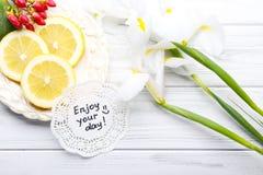Wiadomość Cieszy się twój dzień z pięknymi kwiatami i cytryna pokrajać o zdjęcia stock
