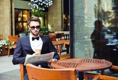 Wiadomość i kawa Młody biznesmen czyta ranku papier, pije kawę w cukiernianym budynku biurowym przestań tła rogalik filiżanki kaw Obraz Royalty Free