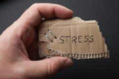 Wiadomości «stresy w ręce na czarnym tle, stary karton fotografia royalty free