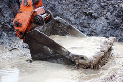 wiadro miarek woda z przykopu na miejscu dla budowy droga po ulewnego deszczu Fotografia Stock