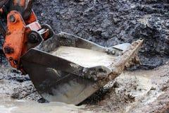 wiadro miarek woda z przykopu na miejscu dla budowy droga po ulewnego deszczu Obrazy Stock