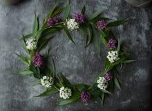 Wianek z kwiatów i zieleni ramą na szarym tle Gałąź wierzby i zieleni liście Szara ponuractwo cementu podłoga obrazy stock