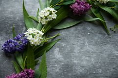 Wianek z kwiatów i zieleni ramą na szarym tle Gałąź wierzby i zieleni liście Szara ponuractwo cementu podłoga obraz stock