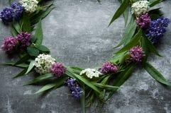 Wianek z kwiatów i zieleni ramą na szarym tle Gałąź wierzby i zieleni liście Szara ponuractwo cementu podłoga fotografia stock