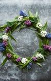Wianek z kwiatów i zieleni ramą na szarym tle Gałąź wierzby i zieleni liście Szara ponuractwo cementu podłoga zdjęcia royalty free