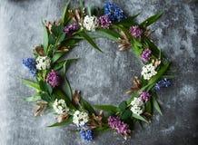 Wianek z kwiatów i zieleni ramą na szarym tle Gałąź wierzby i zieleni liście Szara ponuractwo cementu podłoga obraz royalty free