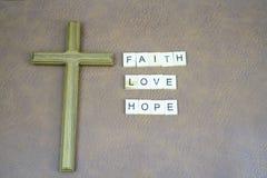 Wiary miłości nadziei listy i święty krzyż na skóra stole zdjęcia stock