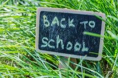 ?wiat?o s?oneczne spada na zielonej trawie i czarnej desce z inskrypcj? Z powrotem szko?a Poj?cie edukacja, szkolenie, fotografia stock